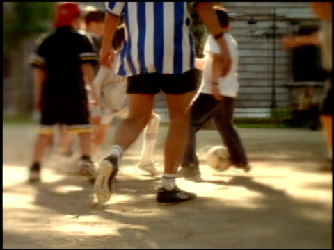 soft focus effect on boys playing football with adult coach in dusty yard, madrid - 2000 stock videos and b-roll footage