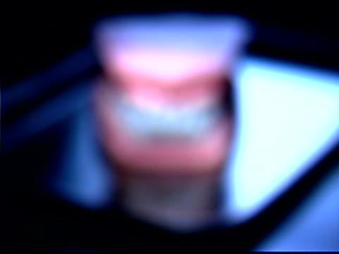 vídeos de stock e filmes b-roll de soft focus image snap zooming into a close of a typodont, a model for proper teeth. - modelo objeto