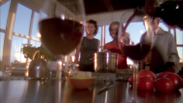 Soft focus low angle zoom out people cooking pasta at dinner party / hands picking up wine glasses in foreground