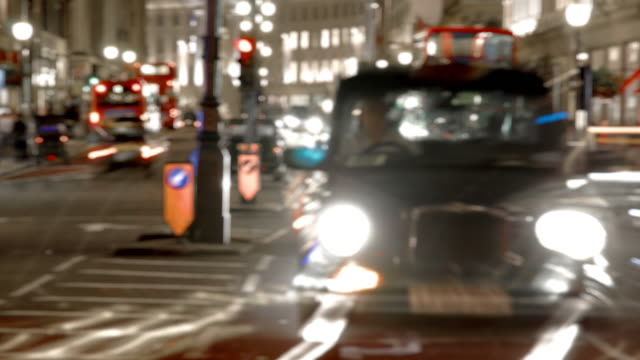 vídeos de stock, filmes e b-roll de a soft focus nighttime view of a busy central london street with cars taxis and buses moving rapidly towards the camera - soft focus