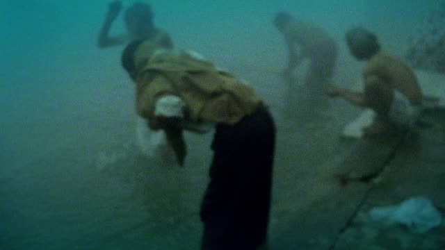 Soft focus slow motion group of men praying and bathing in Ganges in fog at dusk / Varanasi, India