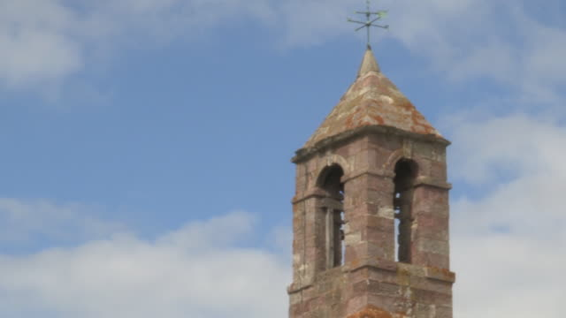 Soft-focus, static shot of clouds moving gently past a weathervane perched on the belltower of St Mary the Virgin Church on the Holy Island of Lindisfarne, Northumberland, UK.