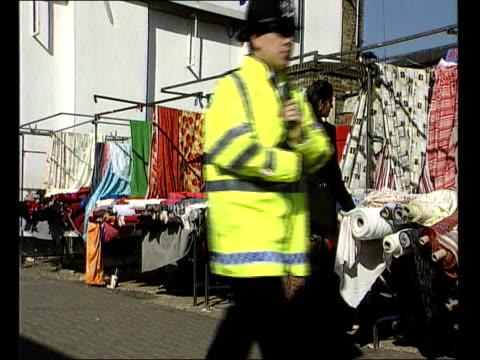 london asian woman standing at market stall as police officer along past lancashire blackburn lms pair of police officers towards - itv evening bulletin stock videos & royalty-free footage
