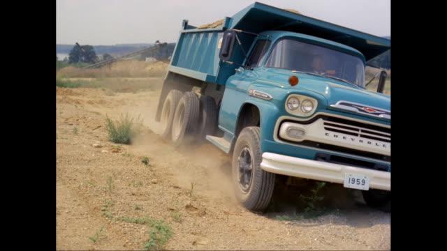 vidéos et rushes de ws pan soil loaded 1959 chevrolet dump truck moving at construction site / united states - chevrolet