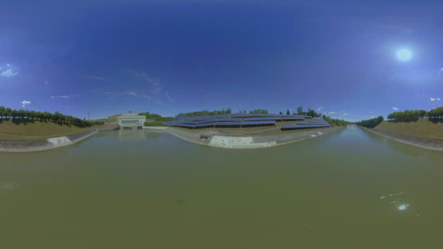 AERIAL VR 360: Solar arrays making power on the bank of a river in sunshine