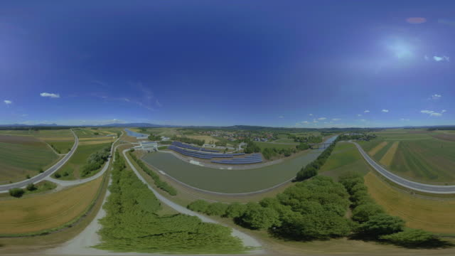 AERIAL VR 360: Solar arrays on the bank of the river in sunshine