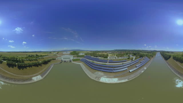 AERIAL VR 360: Solar arrays on the river bank at the hydroelectric power plant on a sunny day