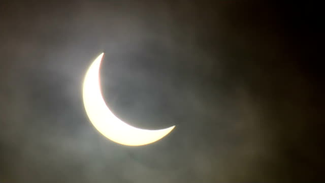 solar eclipse across the uk and europe england bristol gvs partial solar eclipse seen through clouds speeded up timelapse sequence crowds gathering... - clifton suspension bridge stock videos and b-roll footage