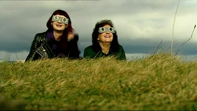 solar eclipse across the uk and europe; scotland: dundee: two women looking at eclipse through protective glasses - スコットランド ダンディー点の映像素材/bロール