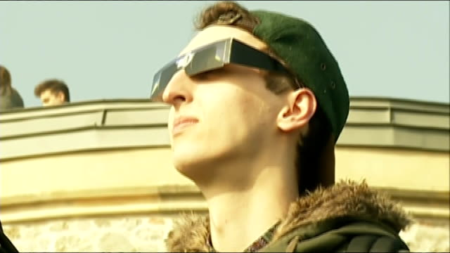 Solar eclipse in Bristol Young man looking at eclipse through protective glasses / young people experimenting with methods of viewing eclipse