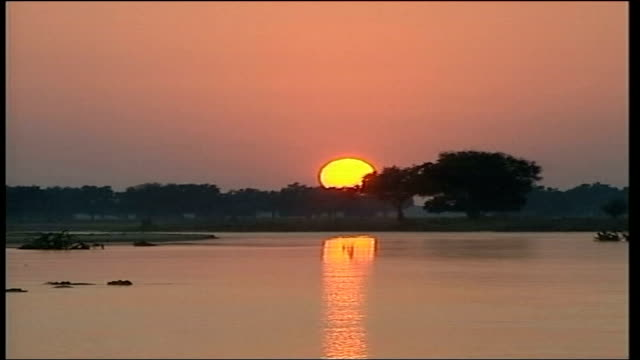 solar eclipse northern orange sun rising behind river zambezi lms tourists standing beside river ms tourists preparing to watch solar eclipse ms line... - solar eclipse glasses stock videos and b-roll footage