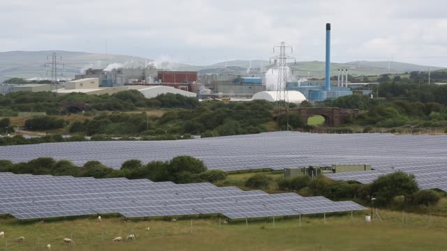 a solar farm and wind turbines next to a manufacturing plant in barrow in furness cumbria uk - built structure stock videos & royalty-free footage