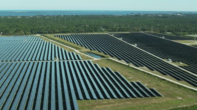 solar farm with water in distance - aerial - ソーラーパネル点の映像素材/bロール