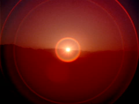 vídeos de stock, filmes e b-roll de solar flares radiate out from a mountain landscape sunset. - brilho solar