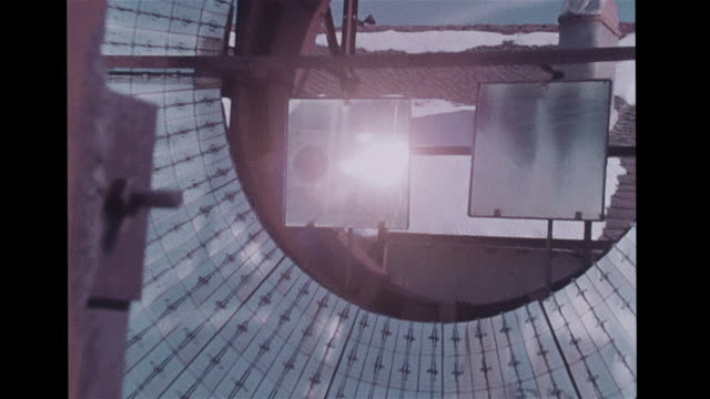 solar furnace facility large movable wall of mirrors, sun reflecting, coils on concave reflector, snow on ground & roof of stone building. global... - reflector stock videos & royalty-free footage