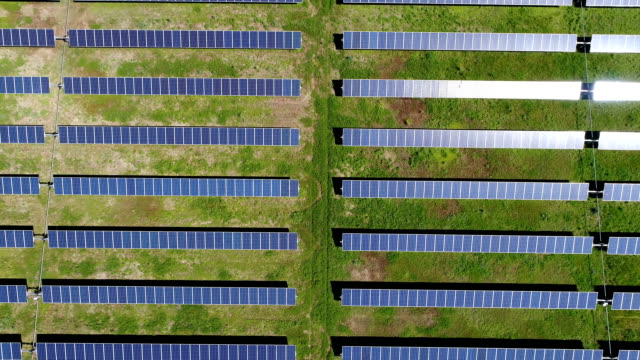 slow motion: solar panel farm creating clean renewable energy - solutions stock videos & royalty-free footage
