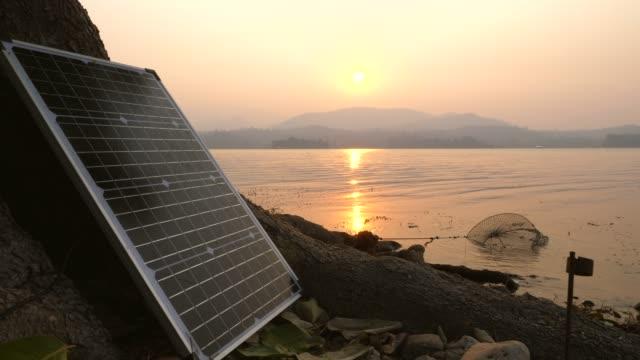 vídeos de stock e filmes b-roll de solar panel on camping with beautiful sunrise, green energy - membro