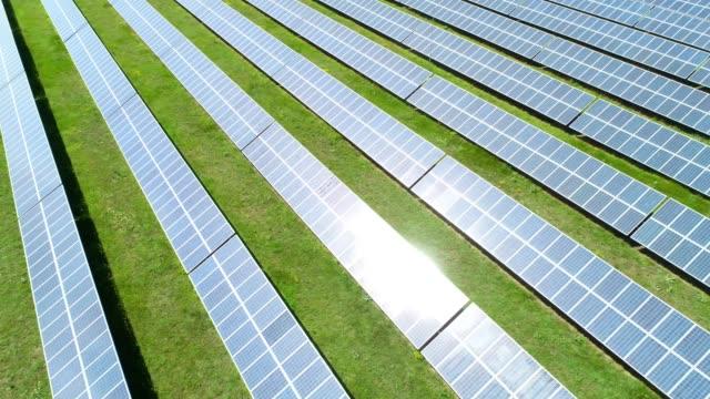 sonnenkollektoren. luftaufnahme über einem solarkraftwerk mit klarem blauen himmel und sonnenstrahlen. - stromnetz stock-videos und b-roll-filmmaterial
