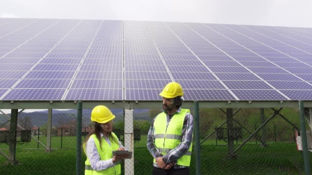 solar panels. electricity engineers working on the field near solar power station with a clear blue sky and sun rays behind them. - power equipment stock videos & royalty-free footage