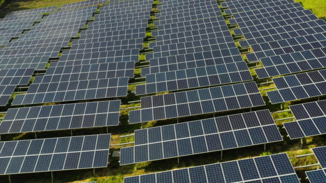 solar panels fields on the green hills - economia video stock e b–roll