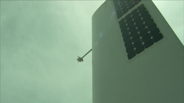 solar panels line one side of a rudder. - windrad stock-videos und b-roll-filmmaterial