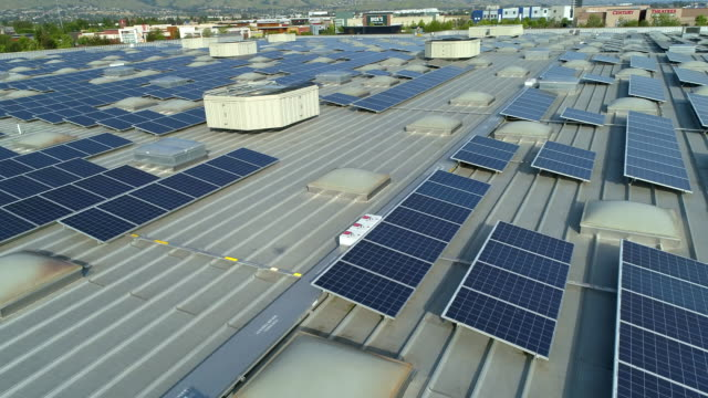 vídeos de stock e filmes b-roll de solar panels on roof of the shopping mall. drone point point of view. - telhado
