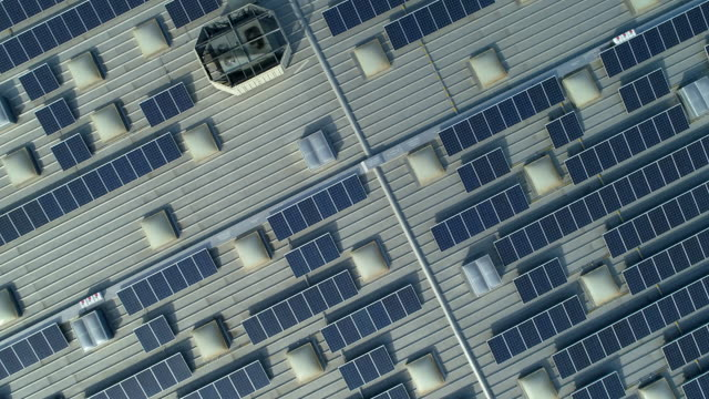 vídeos de stock e filmes b-roll de solar panels on roof of the shopping mall. drone point point of view. - eficiência