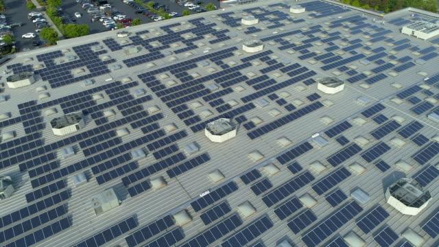 vidéos et rushes de panneaux solaires sur le toit du centre commercial. point de vue de point de drone. - couverture