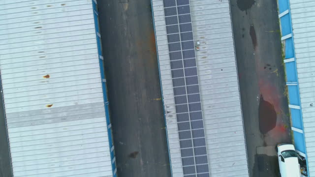 solar panels on the roof of self-storage hangars in long island, new york state, usa. aerial drone video with the descending and panning camera motion. - self storage stock videos and b-roll footage