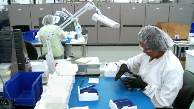 MS Solar plant employee wearing clean room protective clothing leafing through stack of finished solar cells for final quality control inspection at solar manufacturing plant Solarworld, Hillsboro, Oregon, USA