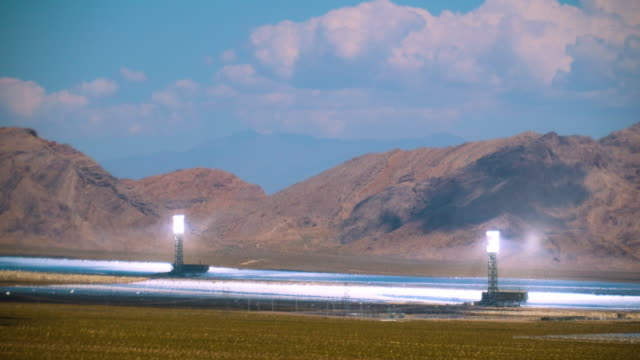 T/L solar thermal power plant with 300000 heliostat mirrors which reflect sun light into solar receiver boilers  set against mountain range and moving clouds overhead   / Ivanpah Dry Lake, California, USA