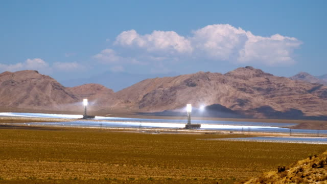 t/l zi solar thermal power plant with thousands of heliostat mirrors directing sun light at solar receiver boilers at top of power towers in mojave desert across from nevada state line  / ivanpah dry lake, california, usa - lake bed stock videos & royalty-free footage