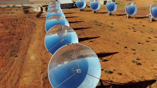 solar thermal power station with parabolic dish reflectors in red dirt field, outback australia, aerial view - south australia bildbanksvideor och videomaterial från bakom kulisserna