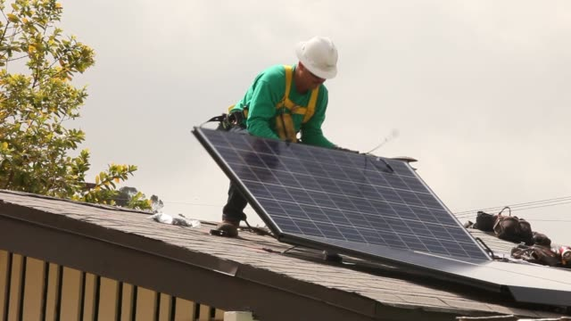 SolarCity employees lift solar panels onto the roof of a home in the Eagle Rock neighborhood of Los Angeles California US Shots of a SolarCity...