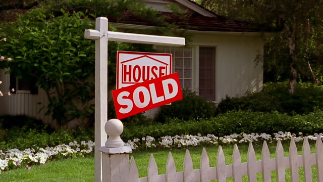 a sold sign stands behind a white picket fence in front of a suburban home. - picket fence stock videos & royalty-free footage