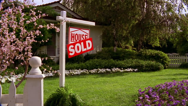 a sold sign stands near a blossoming tree in front of a suburban home. - 住宅購入点の映像素材/bロール