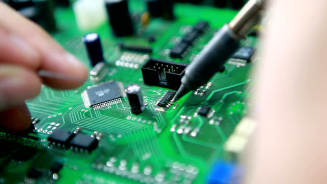 soldering a circuit board - tecnico video stock e b–roll