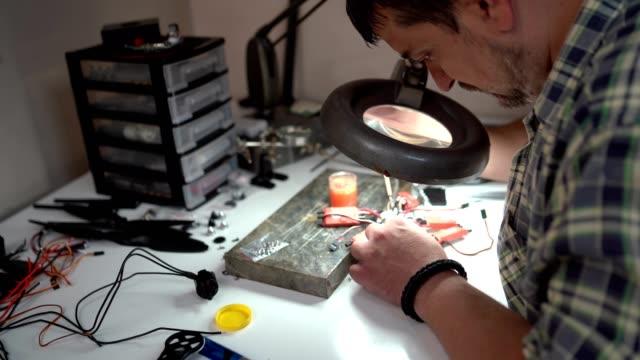 löten von drohnenteilen - elektronik industrie stock-videos und b-roll-filmmaterial