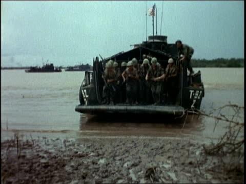 vidéos et rushes de solders exiting an amphibious troop transport / soldiers running onto the beach - véhicule amphibie