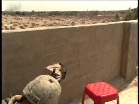 soldier aims his weapon through a hole in a rooftop wall. - al fallujah stock videos & royalty-free footage