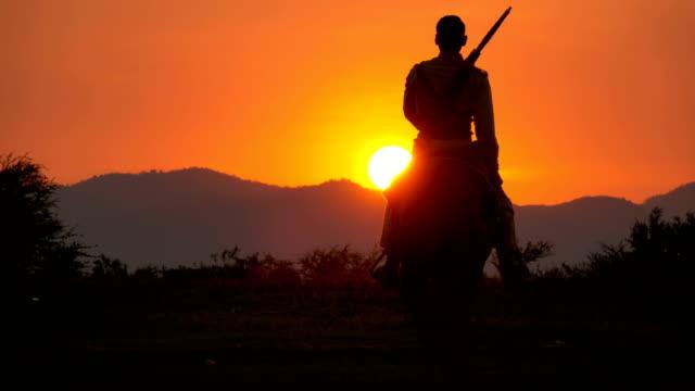 4k soldato e cowboy a cavallo cavalli che camminano verso il tramonto - soldato video stock e b–roll