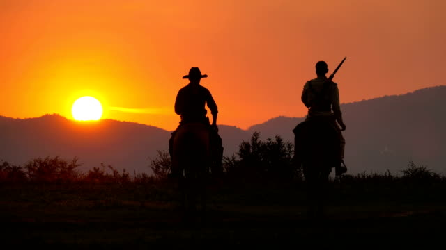 4k soldier and cowboy riding horses walking into the sunset - wild west stock videos & royalty-free footage