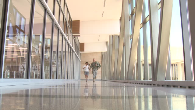 vidéos et rushes de soldier and girlfriend running in airport - couple d'âge moyen