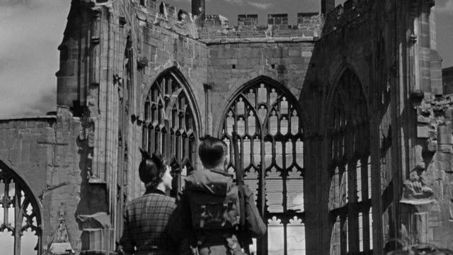 1945 montage soldier and his date walking through skeletal ruins of bombed out cathedral as organ plays, and returning to the street / coventry, west midlands, england - コベントリー点の映像素材/bロール