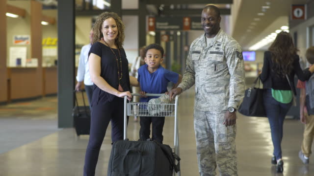 Soldier and his family looking at camera at an airport