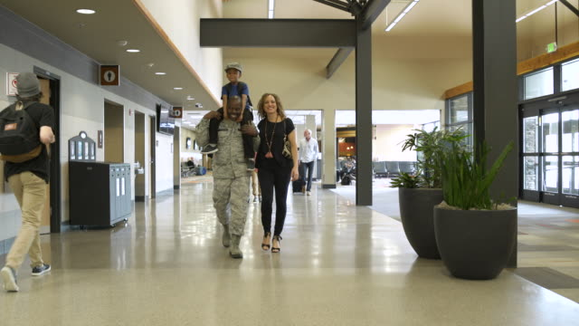Soldier and his family walking at an airport
