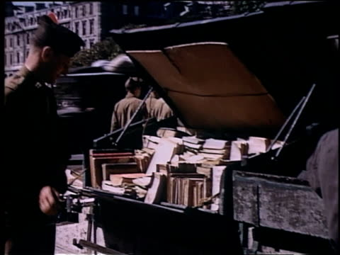soldier approaching and browsing through books stacked in back of truck / soldier leafing through book looks at camera - bookseller stock videos and b-roll footage