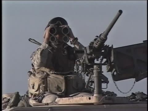 soldier atop a vehicle looks through binoculars. - al fallujah stock videos & royalty-free footage