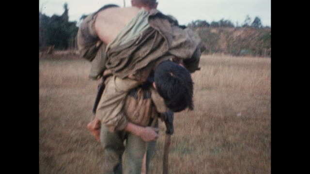soldier carries injured soldier over his shoulder during vietnam war as wounded troops are evacuated from combat zone near the 17th parallel. - produced segment stock videos & royalty-free footage