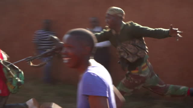 vidéos et rushes de a soldier chases and thrusts his bayonet at a protester in harare during riots in the city - baïonnette